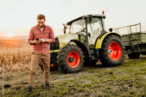 Male farmer working on field using smartphone in modern agriculture - tractor background