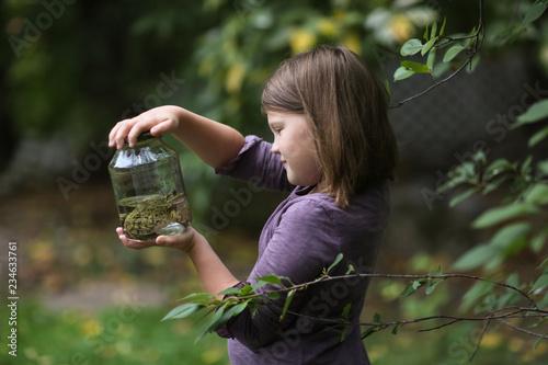 Fotografia Child girl holding jar with frog, naturalist