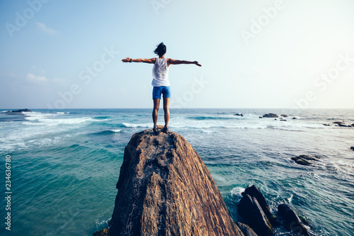 Fototapeta Freedom young woman outstretched arms on seaside rock cliff edge