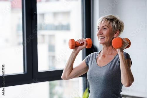Portrait of senior woman lifting dumbbells
