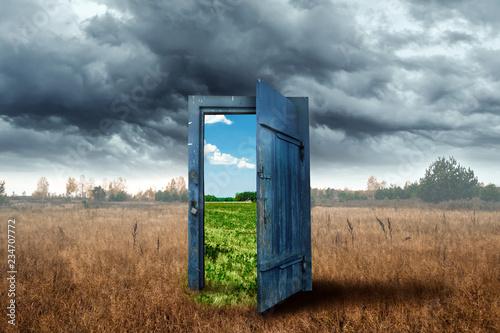 Fototapeta premium Kreatywne tło. Stare drewniane drzwi w pudełku w kolorze niebieskim. Przejście do innego klimatu. Pojęcie zmiany klimatu, portal, magia. Skopiuj miejsce.