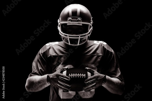 Wallpaper Mural American football player standing with rugby helmet and ball