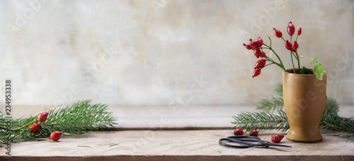 Canvas rosehips and fir branches in a stoneware vase and on a rustic wooden table to ar