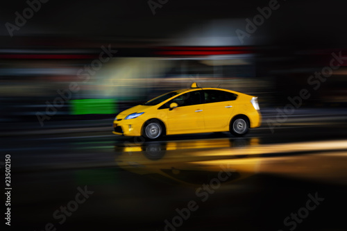 Canvas Print Yellow electric cab in a city enviroment. Panning blur