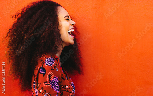 Fototapeta Side view of young woman in floral dress laughing