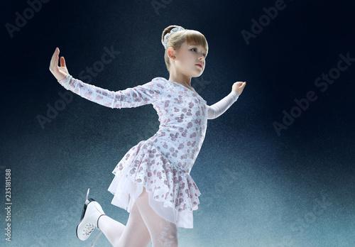 Fototapeta premium Mała łyżwiarstwo figurowe na krytej arenie lodowej. Taniec, sport, zima, ćwiczenia, trening, dzieciństwo, koncepcja mistrza