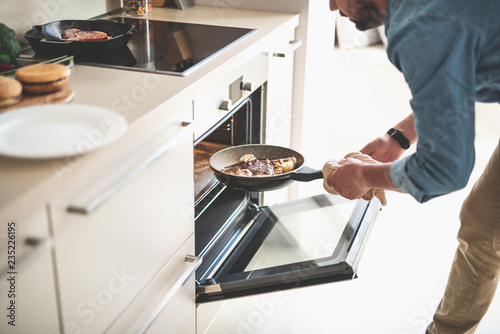 Dinner is ready. Male hands holding frying pan with meat near opened oven