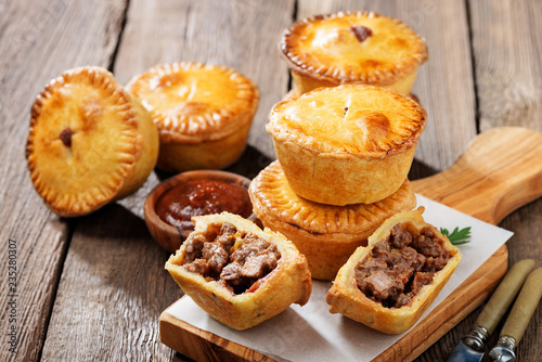 Canvastavla Traditional Australian Mini meat pies from shortbread dough on a wooden board over wooden background