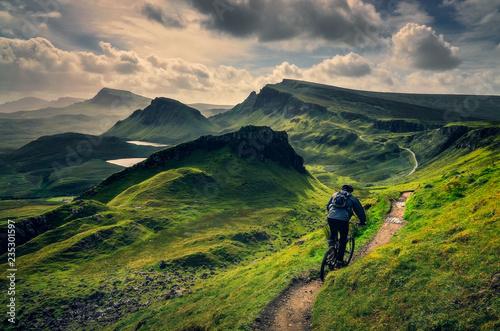 Obraz na plátně Mountain biker riding through rough mountain landscape of Quiraing, Scotland