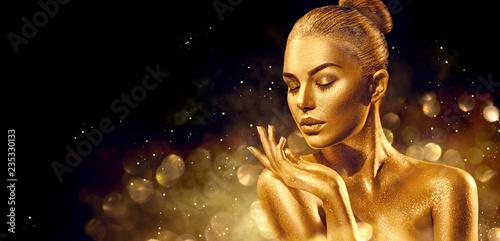 Christmas woman. Golden skin woman portrait closeup. Sexy model girl with holiday golden shiny professional makeup. Golden metallic body