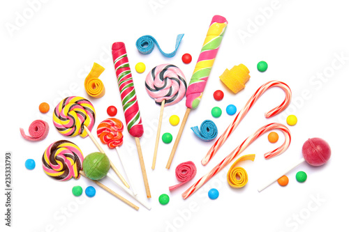Composition with different yummy candies on white background, top view