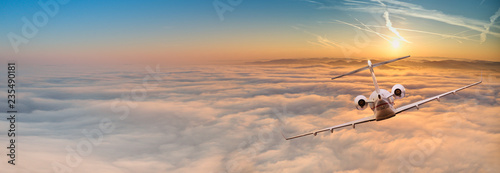 Fotografie, Obraz Private jet plane flying above dramatic clouds.