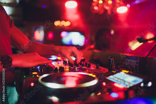 DJ hands on the remote. nightclub. DJ controlling and moving the mixers in music remote.
