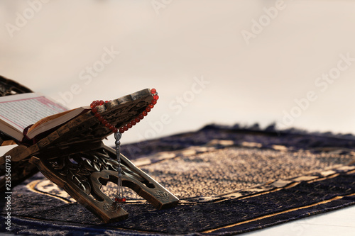 Rehal with open Quran and Muslim prayer beads on rug indoors. Space for text