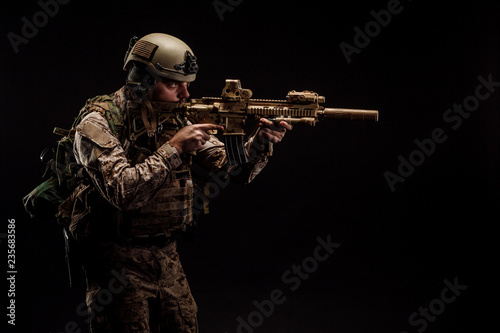 Fototapeta Special forces United States soldier or private military contractor holding rifle