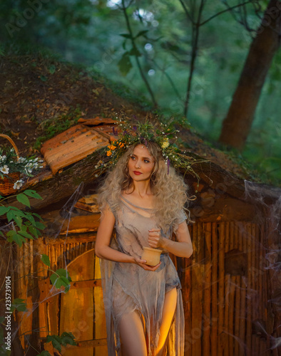 Fotografie, Tablou nice young girl with blond hair with an amazing lush wreath on her head in the forest is shaking herbs