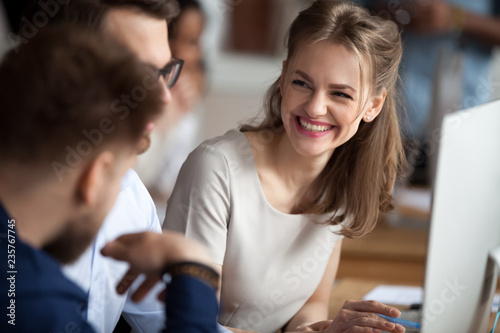 Smiling happy young woman talking with male colleagues at shared workplace, worker laughing at funny joke, reading funny news, excited business success, employees having break, pause