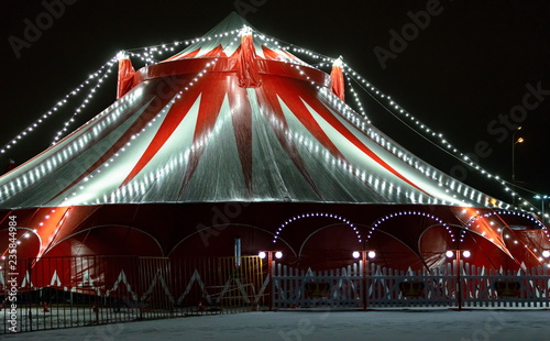 The circus illuminated and decorated with garlands of light bulbs, at night