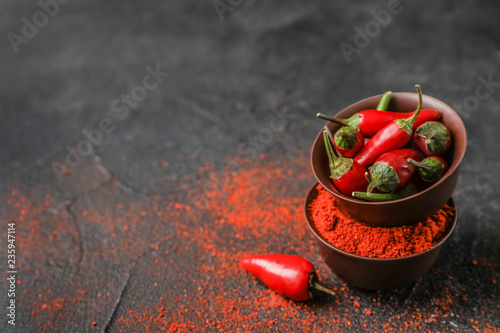 Photo Bowls with raw and powdered chili peppers on dark table