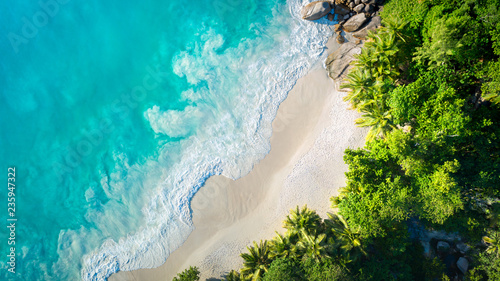 Tropical beach with sea and palm taken from drone. Anse Lazio beach at Praslin island, Seychelles. Vacation holidays concept