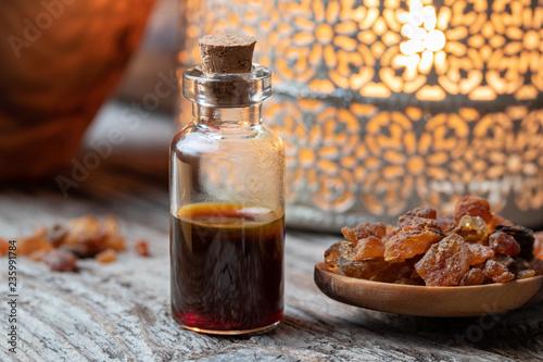 Canvas Print A bottle of myrrh essential oil with myrrh resin on a table