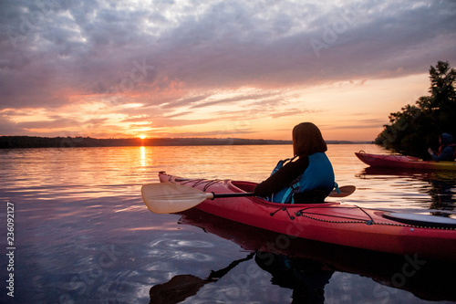 Two people in kayaks on the river on the scenic sunset