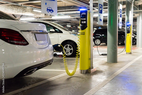 Electric car (new energy vehicle, NEV) is charged from the charging station in the parking lot of the shopping center Fototapeta