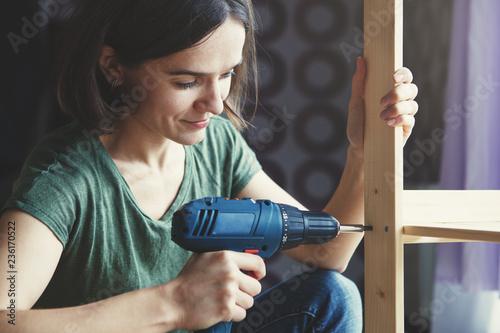 Fotografia beautiful young woman holding screwdriver and repairing or making wooden shelf