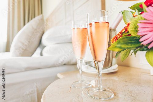 Two glasses of rose champagne in the upscale hotel room. Dating, romance, honeymoon, valentine, getaway concepts