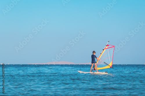 One child learning to windsurf in the open sea waters at beautiful sunset light, close up, windsurfing passtime and school with copy space
