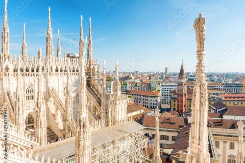 Fototapeta premium Biały posąg na szczycie katedry Duomo i widok na Mediolan