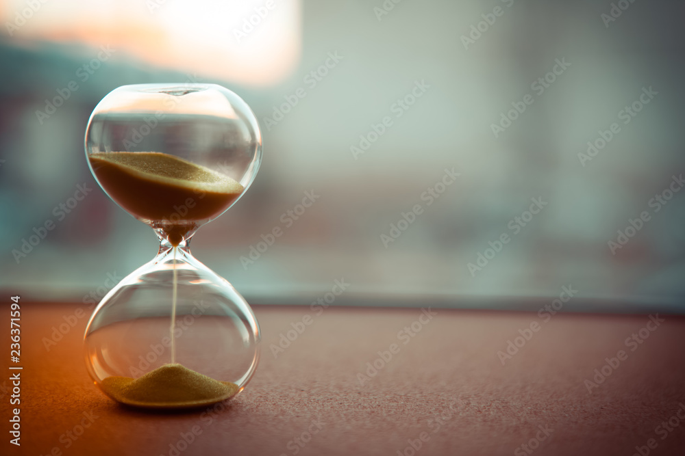 Sand running through the bulbs of an hourglass measuring the passing time in a countdown to a deadline, on a blur background with copy space