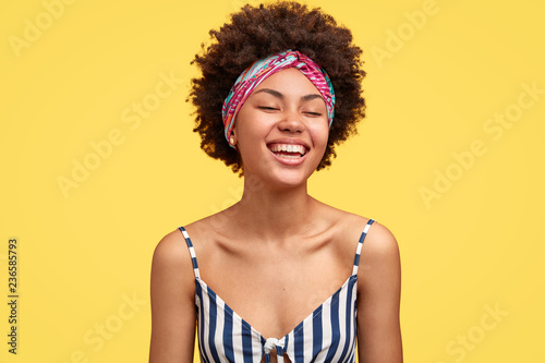 Canvastavla Joyful dark skinned model laughs pleasantly, closes eyes from happiness, recieves wonderful suggestion, being in high spirit during summer trip, wears headband and striped top, poses indoor