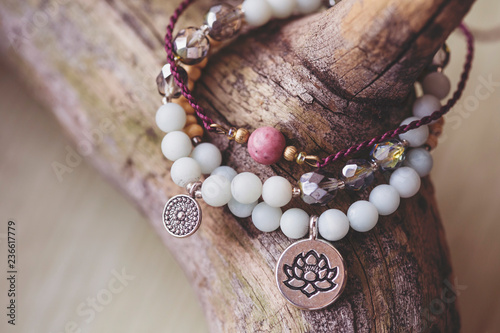 Stampa su Tela Three natural mineral stone beads bracelet on wooden background