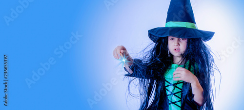 Fotografia Cute little child girl sorceress in mystical gown with a magic wand pronounces witchcraft