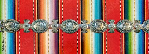 Fotografia Sterling Silver Native American Concho Belt on Brightly Colored Southwestern Pattern Fabric