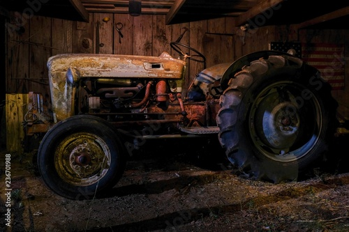 A vintage or antique tractor in an old dimly lit barn at nighttime Poster Mural XXL