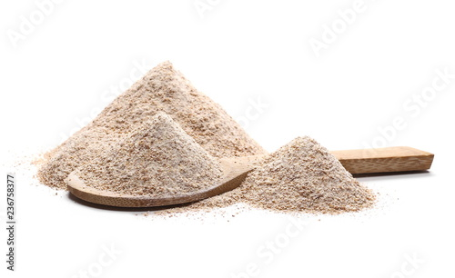 Pile of integral wheat flour in wooden spoon isolated on white background