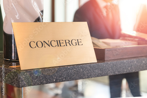 Fototapeta Concierge service desk counter with happy employee staff receptionist working in front of hotel with tourist guest business customer