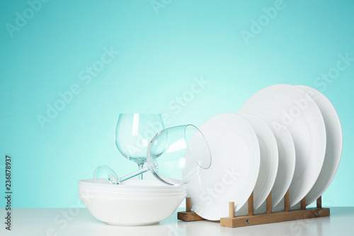 Set of clean dishes and glasses on table against color background