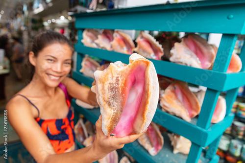 Leinwand Poster Souvenir shop selling conch shells seashells store in Florida, USA travel, Asian tourist woman buying seashell