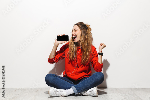 Fotografie, Obraz Photo of cheerful woman 20s singing and holding mobile phone while sitting on fl