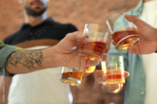 Friends toasting with glasses of whiskey indoors, closeup Fototapeta