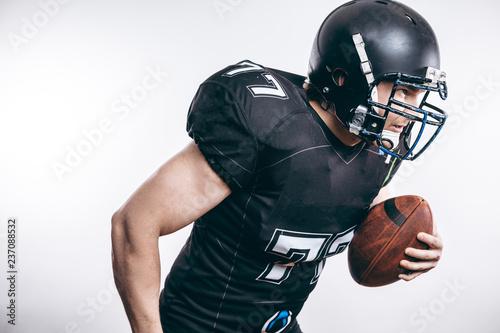 Fotografia American football player wearing black helmet and jersey serving the ball in mot