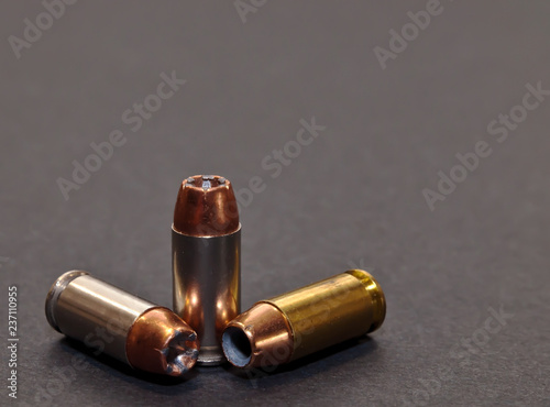 Three 40 caliber hollow point bullets on a gray background Fototapet