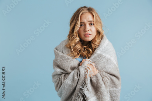 Image of dissatisfied woman 20s wrapped in blanket looking at camera, isolated over blue background