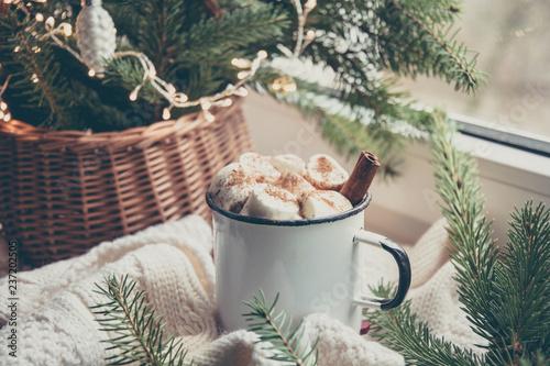 Winter warming mug of chocolate with marshmallow on windowsill with Christmas tree decor.