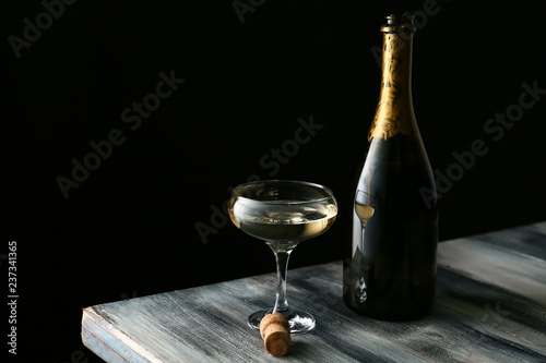 Vászonkép Glass and bottle of champagne on wooden table against dark background