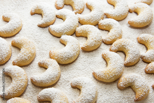 German and Austrian traditional Christmas cookies vanilla crescents on white tray powdered with castor sugar. Beautiful light. Food pattern. Holiday baking concept
