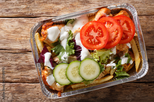 Traditional Dutch fast food kapsalon of french fries, chicken, fresh salad and sauce close-up. Horizontal top view